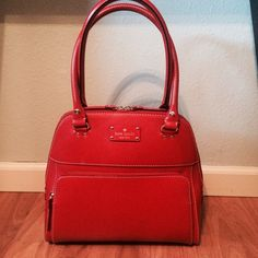 Red Leather Kate Spade Wellesley Maeda Satchel This gorgeous, Christmas Red bag demands attention. Make a statement without ever saying a word. It is all leather, with gold plated details, making it perfect for the holidays (or any season, really!). It features one exterior zip pocket, two interior cell pockets, and one interior zip pocket. Metal feet on bottom of bag to protect the leather. It's professional on the outside, but the fun polka dot interior is sure to keep your youthful side…