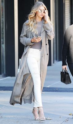 Gigi Hadid wears a gray top, trench coat, ripped skinny jeans, and white heels