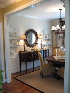 Love it all - the round dining room table, slipcovered chairs, wainscoting and round mirror over antique sideboard. Ahhh one day!