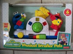 Fisher-Price Sesame Street Musical Stroller Pals [1998] Lights, music and fun sound are activated when child bats at Elmo, Cookie Monster or spinning ball. Also includes squeaker, sliding blocks and teether. Easily attaches to strollers. Plays 6 melodies. Requires 2 AA batteries.  #Fisher-Price #Baby_Product