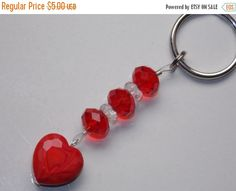 This 24mm Split Ring Keychain was created with faceted Red Glass Rondelles, and Clear Pressed Czech Glass Spacers A Red Lampwork Heart dangles at end