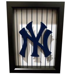 This New York Yankees logo 3D pop art features the iconic Yankees symbol and teams classic pinstripes. The NY Yankees logo is rendered in 3D. The paper cut artwork is hand cut and hand assembled. The baseball artwork comes framed in a black shadowbox frame and is ready to hang. This is the