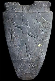 PALETA DE NARMER. Dinástico Temprano, I Dinastía. El Cairo, Museo Egipcio. Placa de pizarra tallada con bajorrelieves, descubierta en en el templo de Horus de Hieracómpolis. Ambas caras tienen grabada en la parte superior dos cabezas de vaca, símbolo de la diosa Bat.  Reverso: Figura del rey Narmer, con la corona blanca del Alto Egipto, golpea a un extranjero con la presencia del dios Horus, sobre un conjunto de papiros que simbolizan el Bajo Egipto.