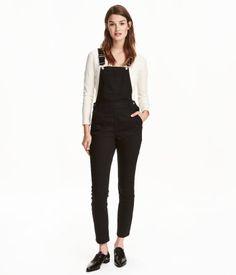 Black. Bib overalls in washed, stretch denim with adjustable straps, bib pocket, side pockets, and back pockets. Fasteners at sides, concealed zip at one