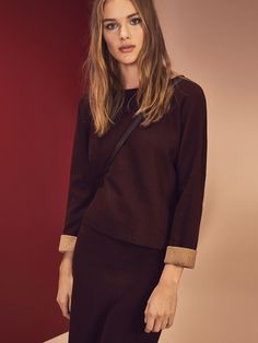 Jersey estilo capa, confeccionado en una delicada mezcla de tejidos. Corte recto, cuello barco y manga murciélago 3/4 con detalle de doblado.