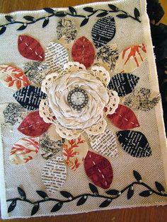 Une couverture décorée de feuilles de tissu autour d'une belle fleur.