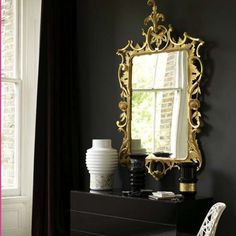 Gold mirror on black wall in a black room