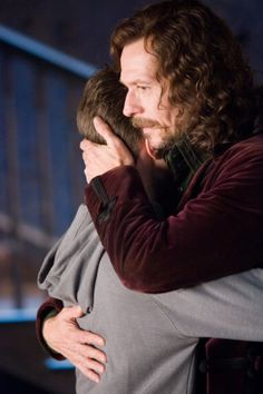 Sirius hugs Harry in Grimmauld Place.