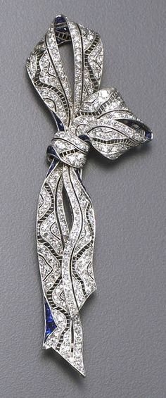 An art deco diamond, sapphire and platinum brooch, circa 1915 the ribbon brooch set throughout with single and old European-cut diamonds and accented with calibré-cut sapphires; estimated total diamond weight: 2.25 carats; length: 3¾in.