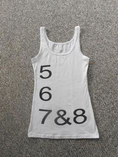 """5 6 7&8! A super soft dance tank top from Next Level apparel brought to you by Contemporary Dance Apparel. Be the center of attention at your studio or convention with this tank top! Silk screened words 5 6 7&8. Sizes small, medium and large.     -Model is 5'9"""" 115 lbs and is wearing a size small"""