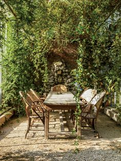 Chestnut chairs sit beneath an arbor dripping with wisteria and passion flowers.