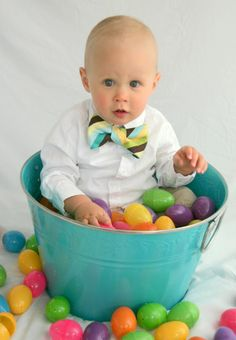 adorable easter picture...white sheet draped over the back of a sofa, pastel bucket, plastic easter eggs, a cute bowtie that compliments the eggs and a cute little guy plopped down in the middle of it all