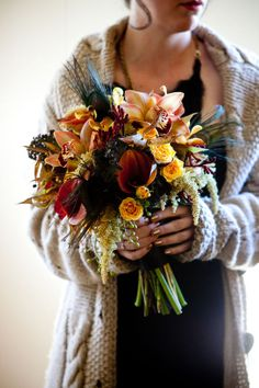 beautiful for a fall wedding...orchids, callas, roses, and unexpected peacock feathers!
