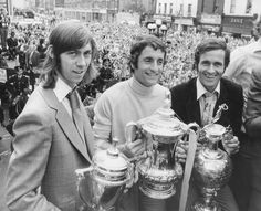Former Arsenal players Charlie George Frank Mclintock & George Graham holding the FA youths cup FA Cup and First Division League title respectively at the Arsenal trophy parade. 1971