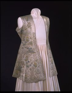 Hunting Coat. 1650, India. Embroidered silk and satin. This splendid coat was made for a man at the Mughal court in the first half of the 17th century. It is embroidered in fine chain stitch on a white satin ground, with images of flowers, trees, peacocks, lions and deer.