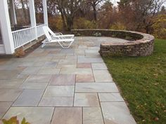 Variegated bluestone patio set in stonedust, random pattern. Pennsylvania fieldstone wall set in cement.