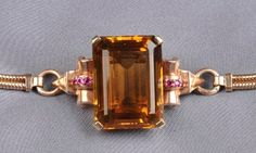 Retro 14kt Bicolor Gold, Citrine, and Ruby Bracelet, set with an emerald-cut citrine measuring approx. 27.00 x 20.00 x 12.80 mm, flanked by circular-cut rubies, completed by a double snake-link strap