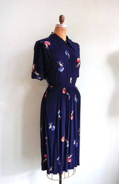 Holy cow! Can you believe this print?? Stunning deep navy blue 1940s rayon dress with dainty hands gilded with ribbons and holding roses, yowza! Features a fitted waist line with an a-line cut skirt and two draped pockets right off of the waist line on either side of the hip. The bodice has a key hole opening with a button clasp at the throats and a large, flat pointed collar! Metal side zip closure. ~ MEASUREMENTS ~  Fits like a medium! | Bust: up to a 40 | Waist: 28 | Hips: open |...
