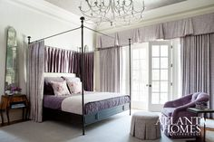 An iron canopy bed and antique mirrors anchor the feminine-hued room.