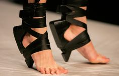Aminaka Wilmont's Spring 2009 Soleless/Souless Shoe. These crazy wooden wedges actually walked at London Fashion Week, tethered like futuristic splints onto models' feet and lower legs. The experimental shoe reverses the heelless craze, doubling the toe-torture by denying any protection as it yanks the heel above the ground, inflicting the burden of balance onto the exposed ball of the foot.
