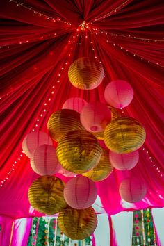 gold and pink paper lanterns, round paper lanterns, red curtain drapes