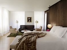 When bringing multiple design elements together, symmetry is key. In this guest room at the London Edition, a walnut-paneled wall evokes the feel of an intimate yacht cabin, which is balanced by the airy feel of light wood floors and linen-and-silk curtains. Globe light fixtures hang unexpectedly low over bedside tables for a cool, modern aesthetic. Just off the bedroom, the sitting area features a green silk rug topped with tufted upholstered seating by George Smith. A Hendrik Kerstens…