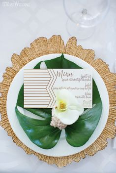 Tropical place setting with a gold charger plate and gold wedding menu! TROPICAL WEDDING IN THE CITY www.elegantwedding.ca