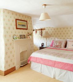 The owner ambitiously chose to wallpaper the undulating walls in the guest room, using a design by Nina Campbell. A homemade quilt adorns the bed, along with some of her pretty floral cushions. The table lamp's shade was a gift, and the base is an upcycled junk-shop find