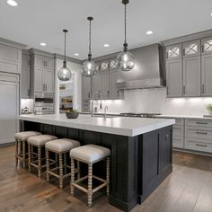 A large gray contemporary kitchen. Gray cabinets and white backsplash and white countertops. Brown wood flooring. Black glass light fixture. Farmhouse bar stools. Photography by Indy 360 Photography.  Kitchen Cabinets Light Wood, Kitchen Cabinets Grey And White, Black And Grey Kitchen, Grey Kitchen Floor, Light Gray Cabinets, Light Grey Kitchens, Brown Cabinets, Brown Kitchens, Home Kitchens