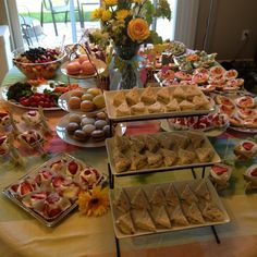 Cucumber tea sandwiches, individual strawberry shortcakes, macaroons, fruit salad, bagels with flavored cream cheese, and cookies like pepperidge farms Milanos or chessmen dipped in chocolate All on platters or trays on white table cloth http://pinterest.com/pin/5770305746706654/