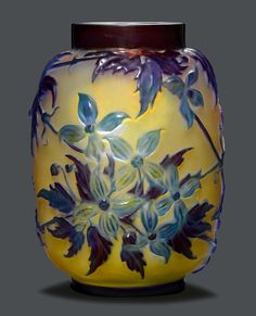 EMILE GALLE VASE SOUFFLE, circa 1920 Yellow glass with blue overlay and etching. Cylindrical vase, decorated with clematises. Signed Gallé. H. 24.5 cm.