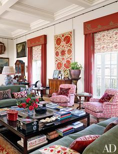 In the drawing room, a suzani panel from Turkmenistan hangs between windows curtained in a Holland & Sherry wool hopsack with appliquéd pelmets and borders; Robert Kime fabrics were used for the Roman shades and the Victorian club chairs, which are accented with antique pillows.