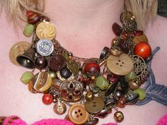 Awesome necklace with lots of vintage and new wood plastic and brass buttons. Necklace also includes wooden and plastic beads and chunky glass faux pearls with antiqued brass bead caps, charms and findings.