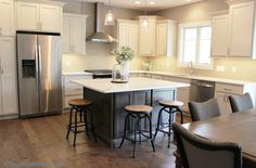 Light gray painted kitchen with gray stained island and Whirlpool appliances. Kitchen by Village Home Stores for Wood Builder Ltd. | VillageHomeStores.com