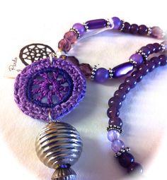 Collar de 54cms, con piezas de cristal facetado violeta transparentes, bolitas cristal opaco violeta, resinas variadas, entrepiezas metálicas intercaladas. Rematado con : Rosetón de 3 violetas en croxet,pieza resina y pompón violeta. 23€