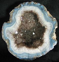 An unusually shaped coconut type geode from Chihuahua, Mexico. Has nice blue and white fortifications surrounding a smoky-quartz center..