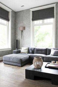 canapé d'angle gris, sol en parquet clair, grandes fenêtres, salon plein de lumière