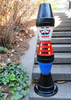 Cute, Christmasy...and made of simple clay pots! Make this festive doorstep soldier for $30-$50.  #christmasdecor #diychristmas