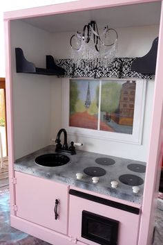 DIY Christmas Gift Idea ~ Small entertainment center made ino a Chic Play Kitchen... love the faux chandelier!