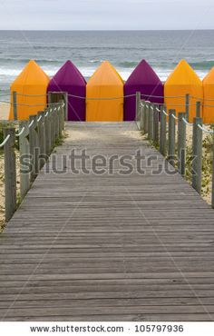 stock photo : Wooden walkway over the sand dunes to the beach and colorful tents