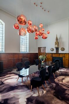 Tom Dixon's Melt Copper pendant lights installed above Tom Dixon's Pylon table and copper-legged Wingback dining chairs, in the vestry of 18th century St James Church