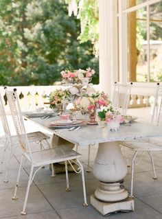mismatched pedestals, marble topped table and pretty fru-fru girlie table ware. Looks like a girls lunch to me.