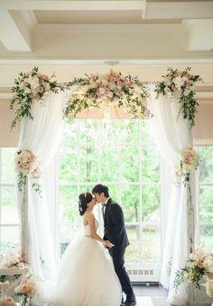 jolie décoration de la salle de réception, arche mariage avec voilage et des bouquets de fleurs