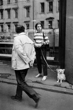leica; 1985; Street; Nevsky Prospect; Leningrad; two; girl; Man; dog; shaggy; animal; average shot; 20 years; 50 years; Russian; walking; sitting; striped sweater; jacket; pants; clock; the leash; a bag; hands in pockets; hands behind back; aeroflot; showcase; lamp; reflection; documentaryphotography sovietphotography; streetphotography; bnwphotography; magnumphotos