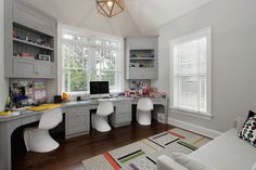 Kids homework room boasts wall to wall built in desks for three paired with white Panton Chairs.