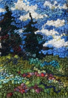 Scenery rug hooking by Deanne Fitzpatrick. Dark green trees, bright blue cloudy sky, colorful landscape.