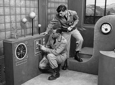 In the early days (1949 - 1952) of CAPTAIN VIDEO, the controls the characters pretended to adjust were painted onto cardboard or very thin plywood. When Olga Druce became producer in late 1952, she insisted that the actors have real knobs and levers to play with.  In this shot made  just after Al Hodge took over the role, he can't do much but point.  [Note the real pressure gauge to the right, however.]