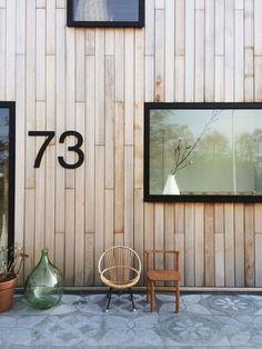 verticale beplanking + uitspringende raamprofielen + huisnummer