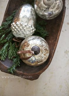 Mercury glass baubles in wooden bowl with greenery
