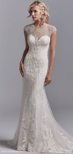 This vintage-inspired wedding dress features a tulle overlay accented in geometric lace motifs with beading and pearls, creating an illusion jewel over sweetheart neckline, illusion cap-sleeves, and an illusion scoop back. Lined with Inessa Jersey for a luxe fit. Finished with pearl buttons and zipper closure.